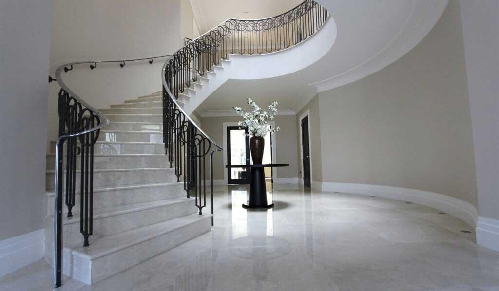 scara de interior in spirala imbracata cu marmura si cu balustrada din fier forjat